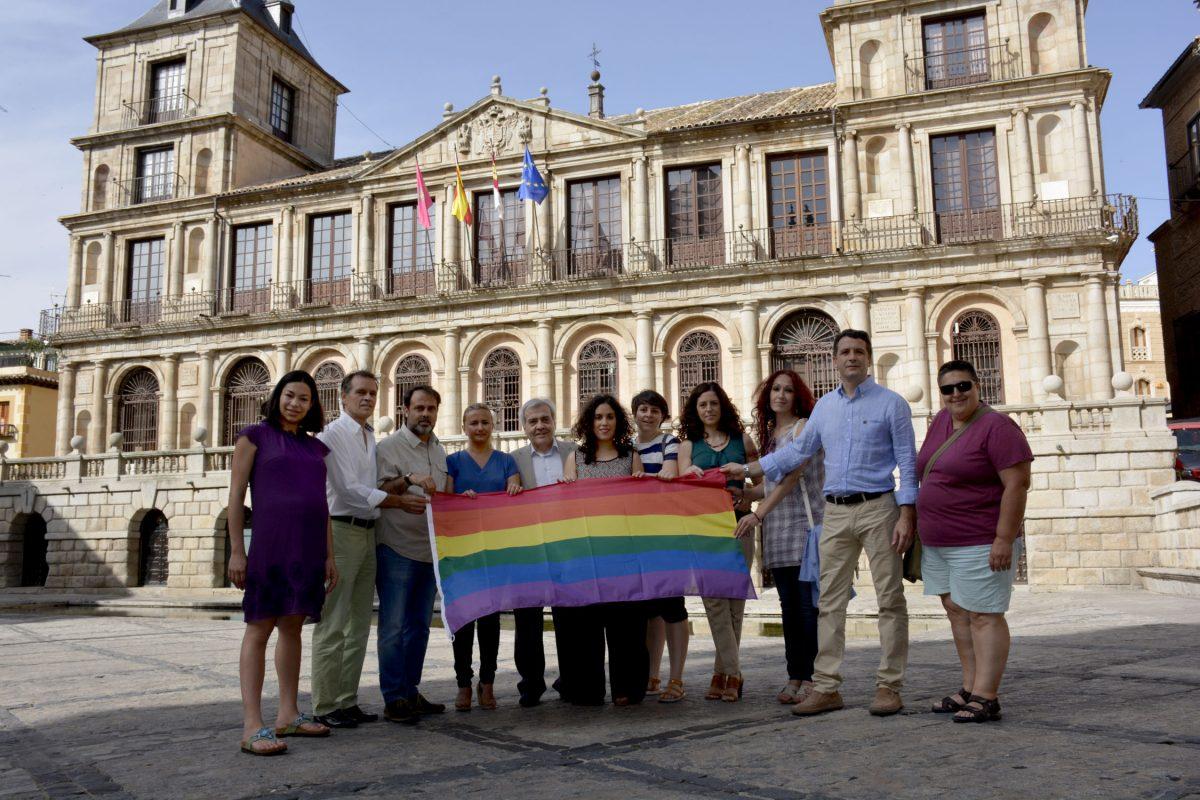 http://www.toledo.es/wp-content/uploads/2016/06/dia_orgullo01-1200x800.jpg. La bandera arcoíris ondea en el balcón del Ayuntamiento con motivo del Día Internacional del Orgullo LGTBI