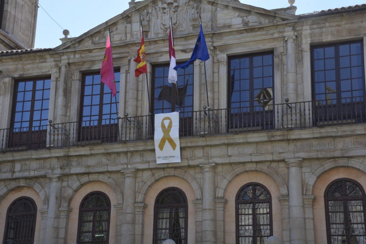 https://www.toledo.es/wp-content/uploads/2017/09/lazo_afanion_01-1200x800.jpg. El Ayuntamiento luce en su balconada un lazo dorado con el que se suma a la campaña de concienciación del cáncer infantil