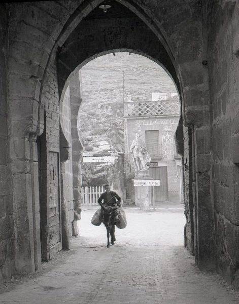 080-AKE_122_Un burro cargado por la puerta exterior del puente de San Martín